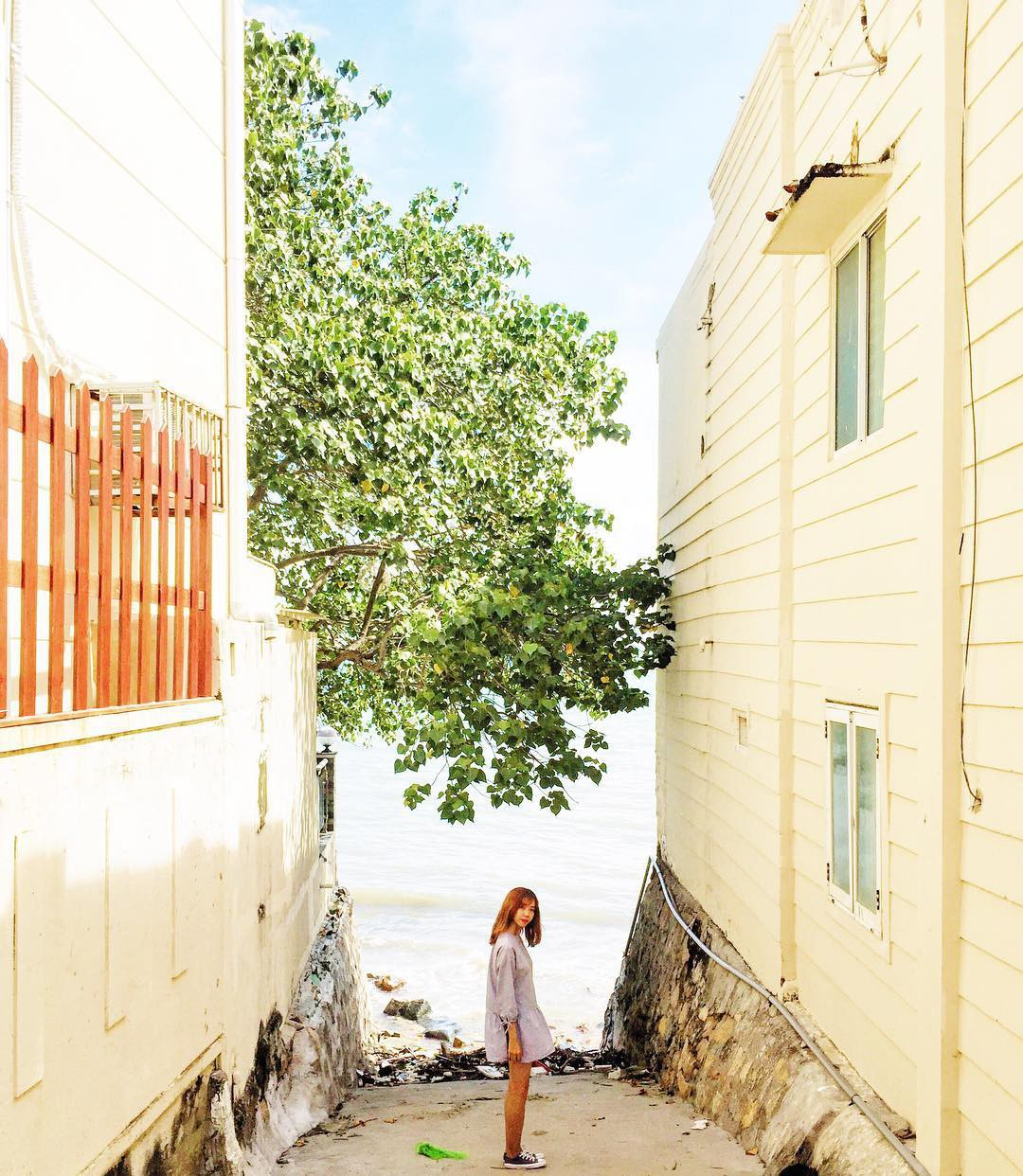 A girl posing along the alley leading to a beach