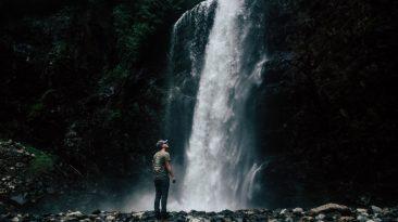 homem contemplando cachoeira