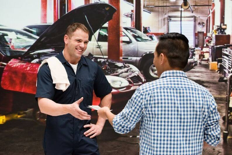 Mechanic works with a customer at automotive franchises garage