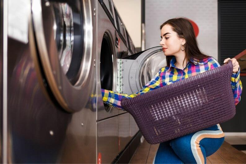 Woman loads clothes into washer at a popular laundromat franchise