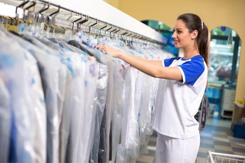 Female employee looks through dry cleaning rack to find customer's clothes.