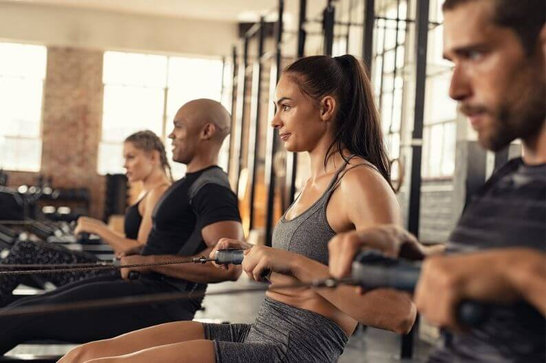Group working out on a water rower at a CITYROW gym franchise