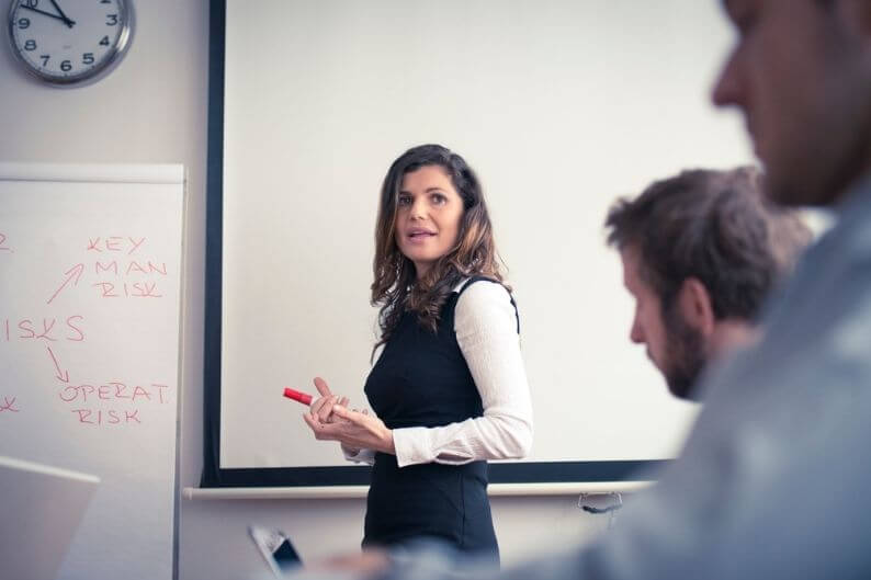 Woman teaches business students about business risks and how to mitigate them.
