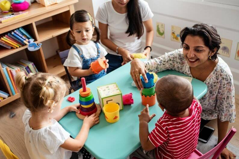 Woman playing with children who are spending the day at a top daycare franchise.