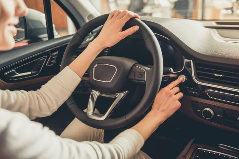 A customer test drives her future car at a dealership specialty franchise.