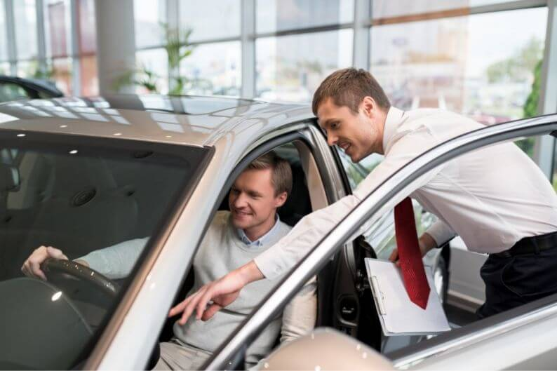 A car salesman shows off his product to a potential customer.