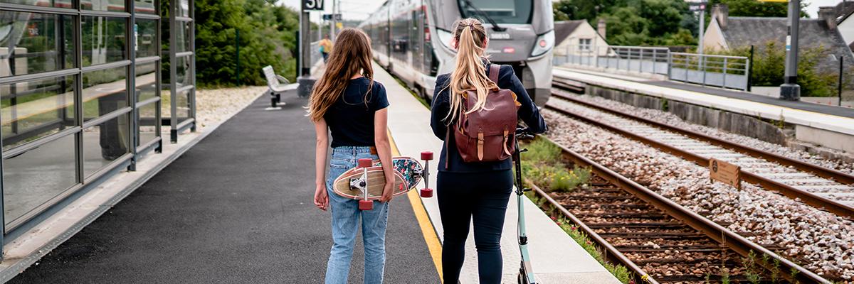 Deux femme avec skate et trottinette à la gare