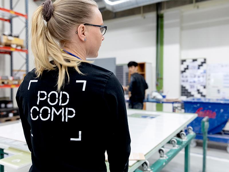 Kvinna framför arbetsbord på Pod Comp.