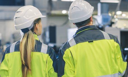 Kvinnlig och manlig arbetare i industrimiljö.
