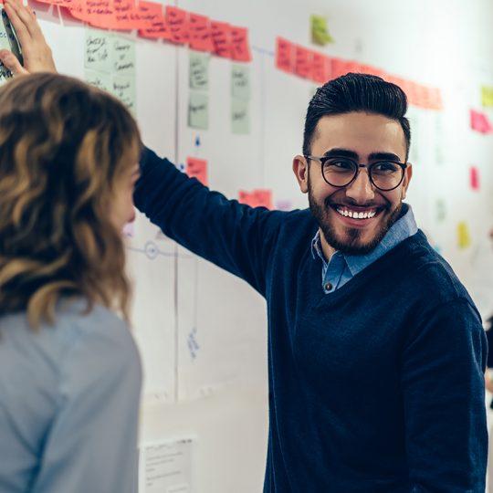 Leende man samarbetar med kollegor för att skapa presentation på en whiteboard.