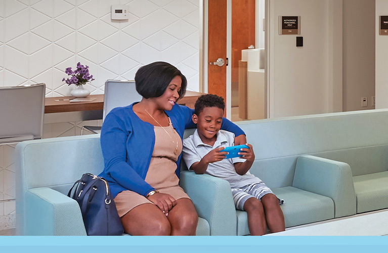 Mom and child at a local UHealth Jackson Urgent Care center, sitting in the waiting room
