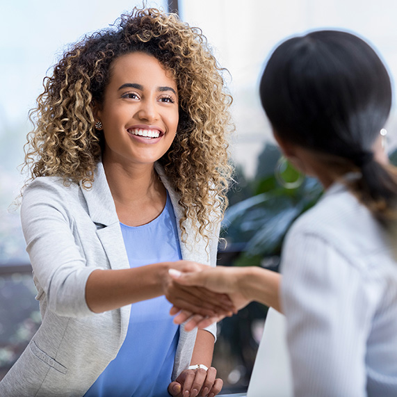 Businesswoman shakes hands with a female interviewer during a job interview.