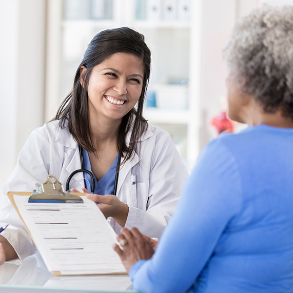 Physician smiling at a patient as she hands her a document to fill out