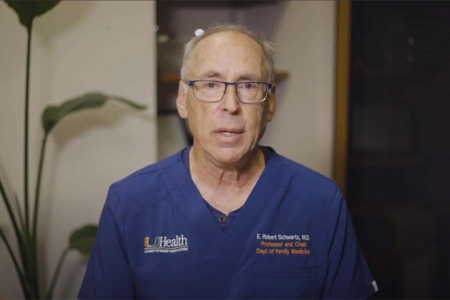 E. Robert Schwartz wearing blue scrubs and glasses, he's speaking on camera