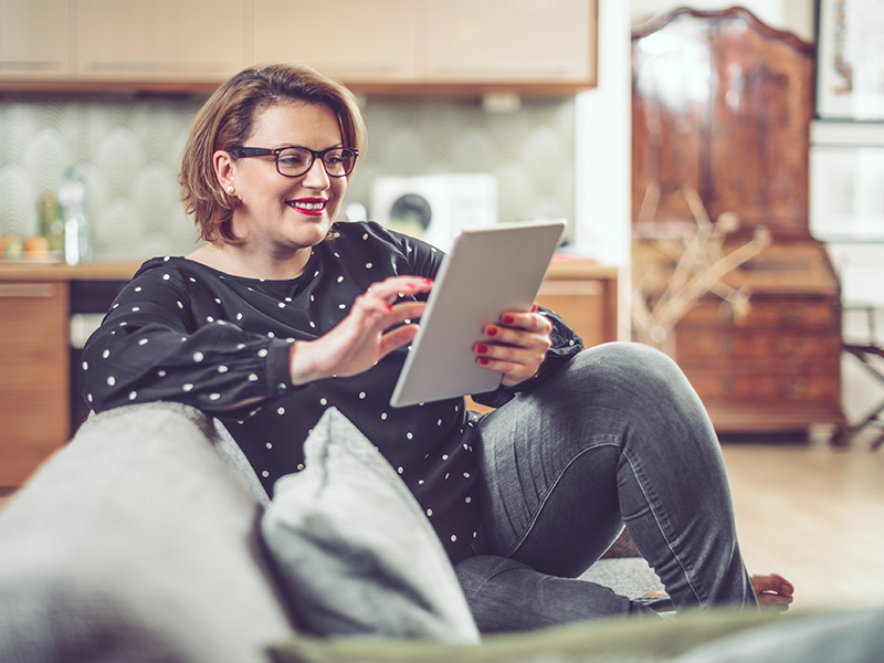 Woman using her tablet as she sits on her couch