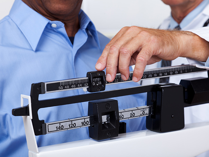 Closeup of a man getting his weight checked by a physician