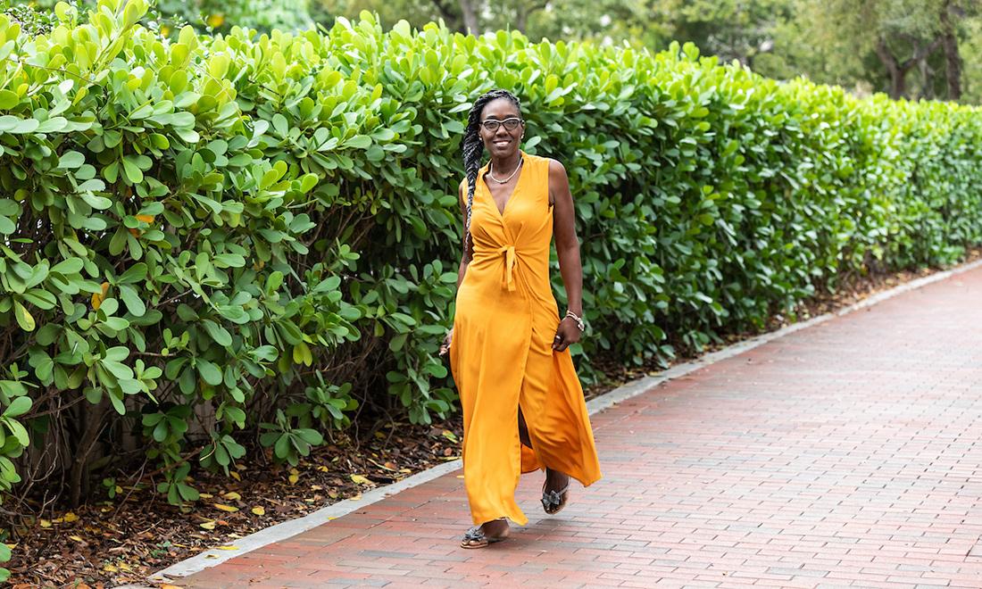Robin walking, she is wearing an orange dress and smiling