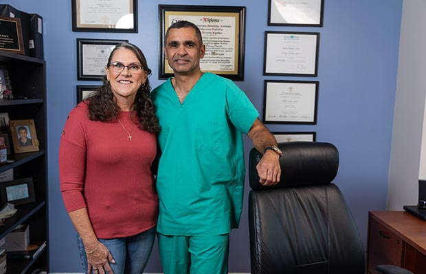 Woman and physician standing next to each other and smiling at the camera