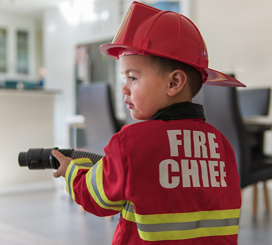 A 3-year old boy dressed up in a fireman costume using a vacuum cleaners hose to pretend he is putting out a fire