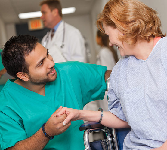 Male nurse holding a female patients hand who is on a wheelchair