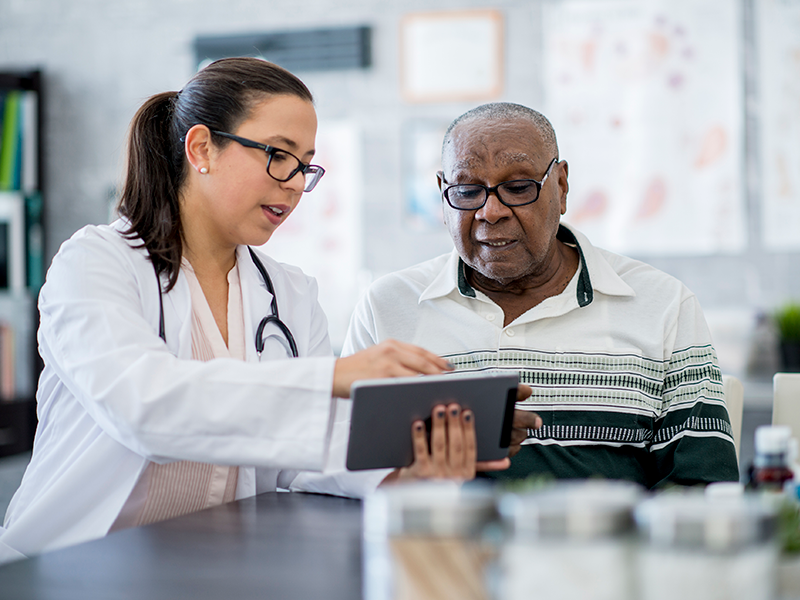 Senior man sitting next to a physician who is going over something with him on a tablet