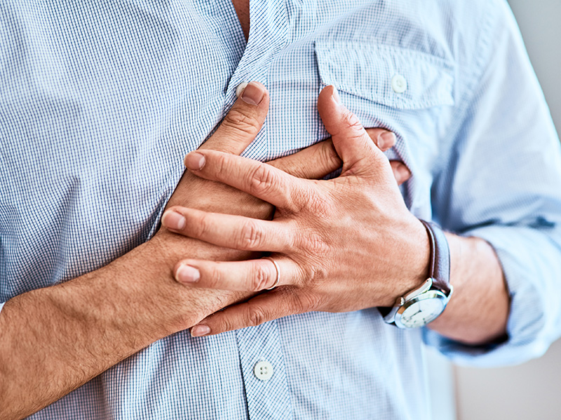 Closeup of a man holding his chest in discomfort