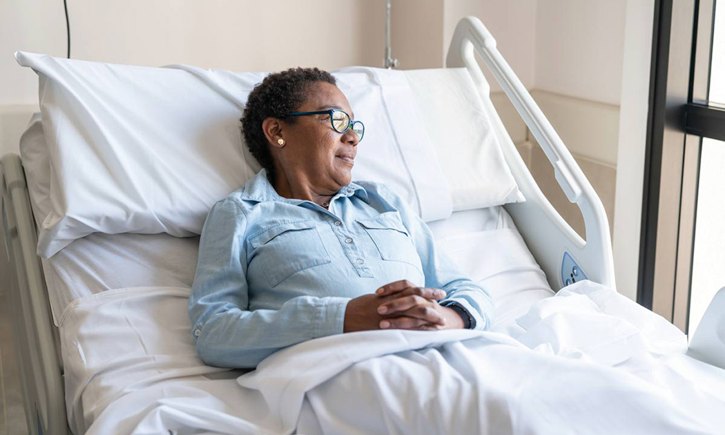 An older woman laying in a hospital bed smiling as she looks out the window