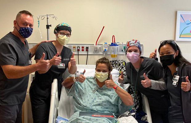 Four medical professionals and a woman who is on a medical bed holding their thumbs up, they all wear face masks