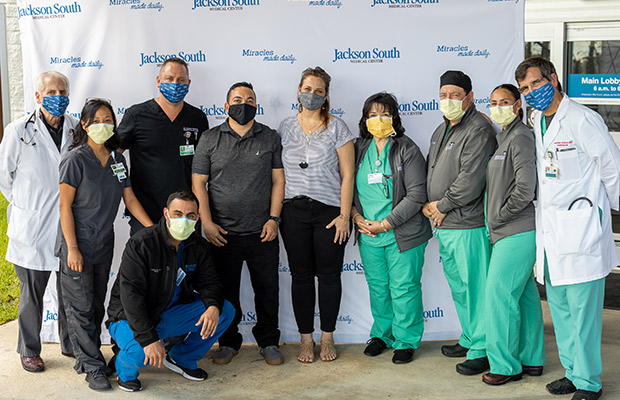 Medical professionals, a men, and woman, wearing face masks and taking a picture