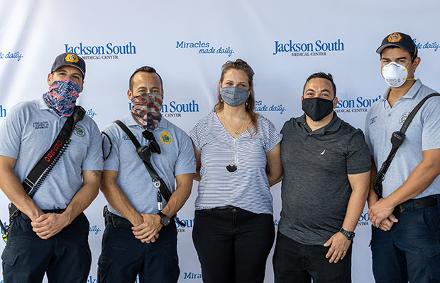 Three medical professionals, a men, and woman, wearing face masks and taking a picture