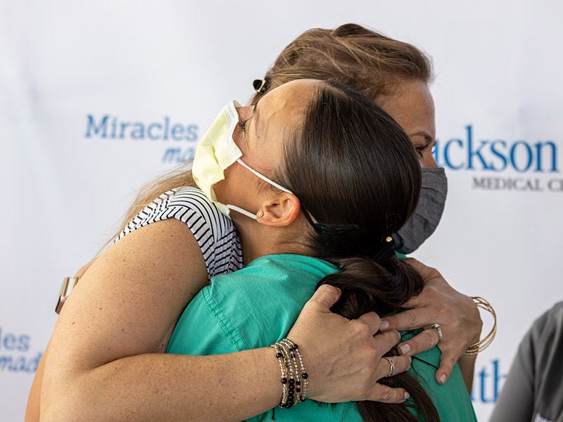 Women wearing a mask hugging a medical professional who is also wearing a face mask