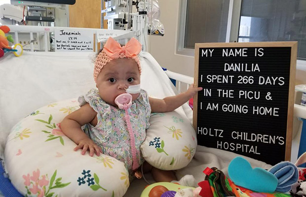 Baby with a sign that says she is going home
