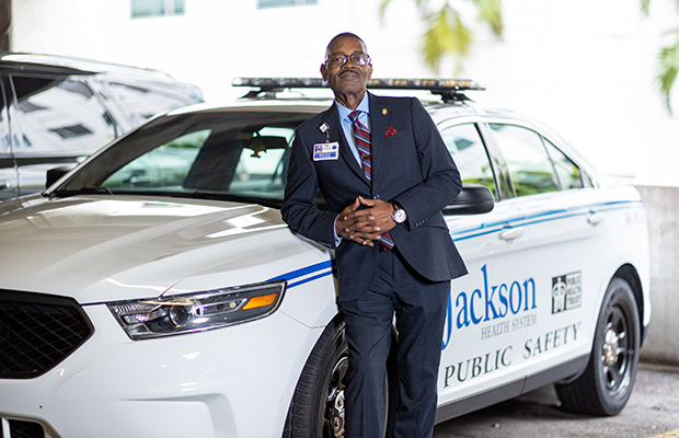 An outdoors image of Robert Davis standing, smiling, and leaning on a Jackson Health System public safety vehicle