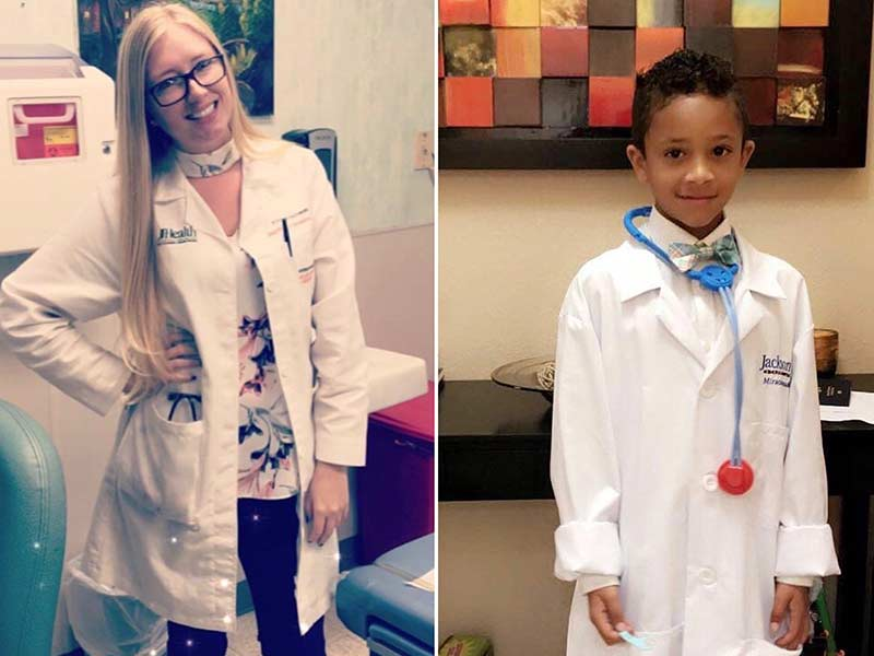 A physician on the left smiling, she has long blonde hair and wears a white coat. A young boy on the right, he wears a white coat and smiles.