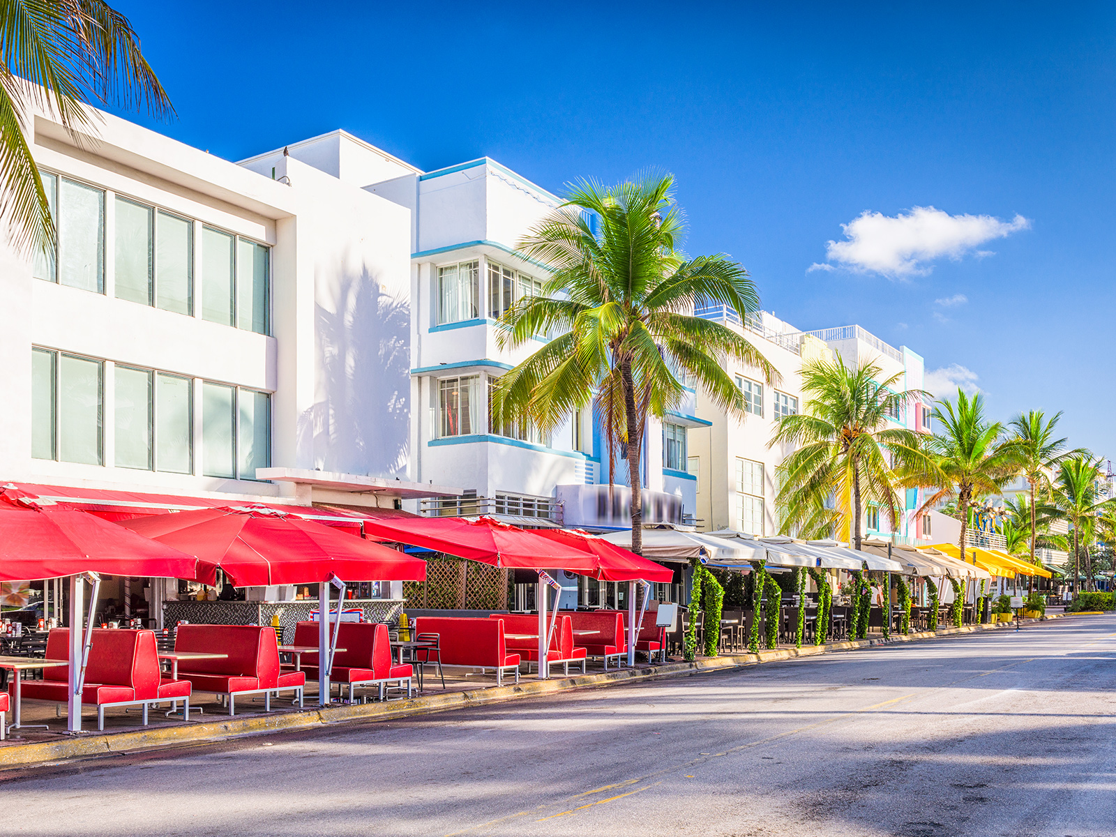 A view of multiple buildings in Miami Beach,the buildings are colorful, there is sitting and palm trees outside
