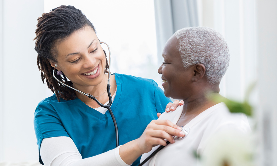 Nurse smiling as she uses her stethoscope to listen to a patients heartbeat, the patient is smiling back