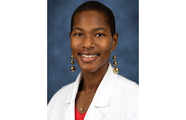 Headshot of Alana J. Arnold, she is waring a white coat and a bright red blouse, she has on long gold earrings