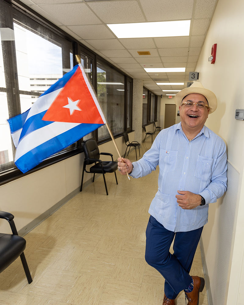 A man smiling at the camera, he wears a tan hat, blue striped shirt and holds a Cuban flag