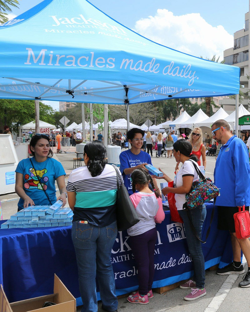 A boot outdoors surrounded by people who are speaking to two professionals, the booth reads Jackson Health System, Miracles made daily