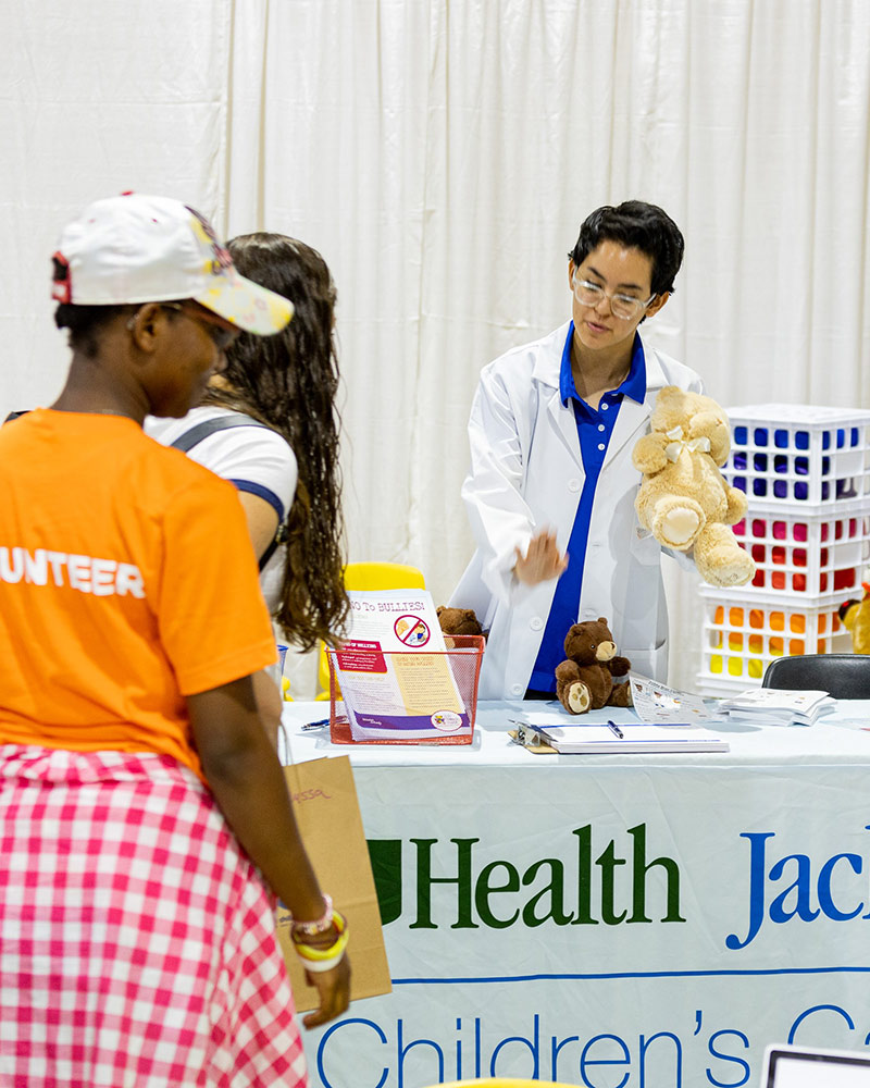 A medical professional at a booth, they are holding a teddy bear and speaking to a woman