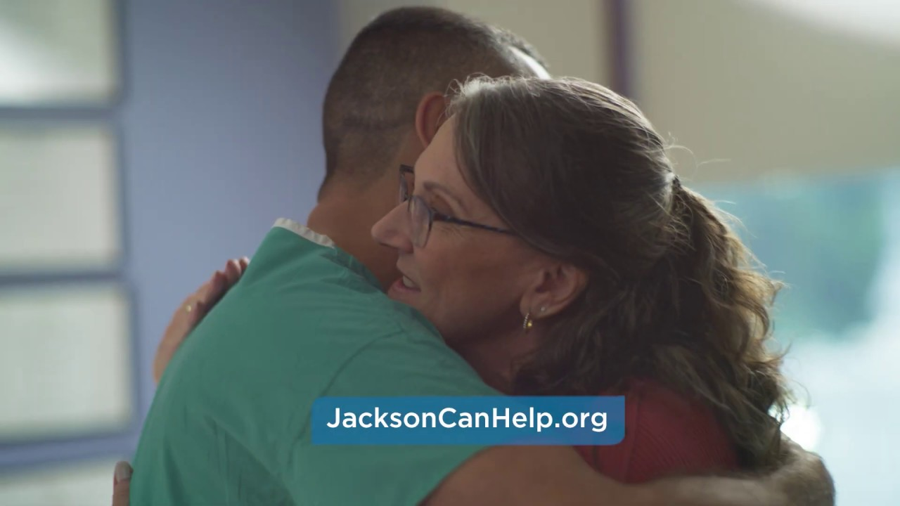 A physician and smiling patient hugging. Text on the image says JacksonCanHelp.org.