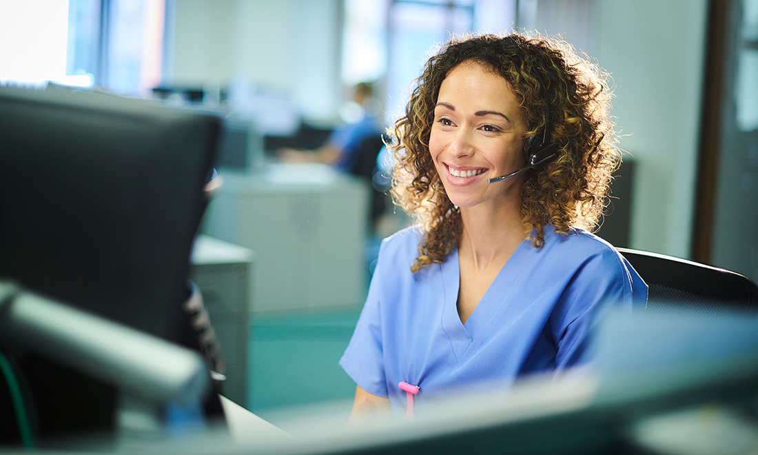 Smiling woman answering a hotline in a medical office