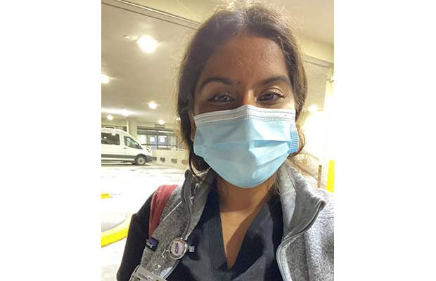 A closeup of a medical professional, she is standing outside a medical building, she has on a face mask, dark blue scrubs, and a gray jacket