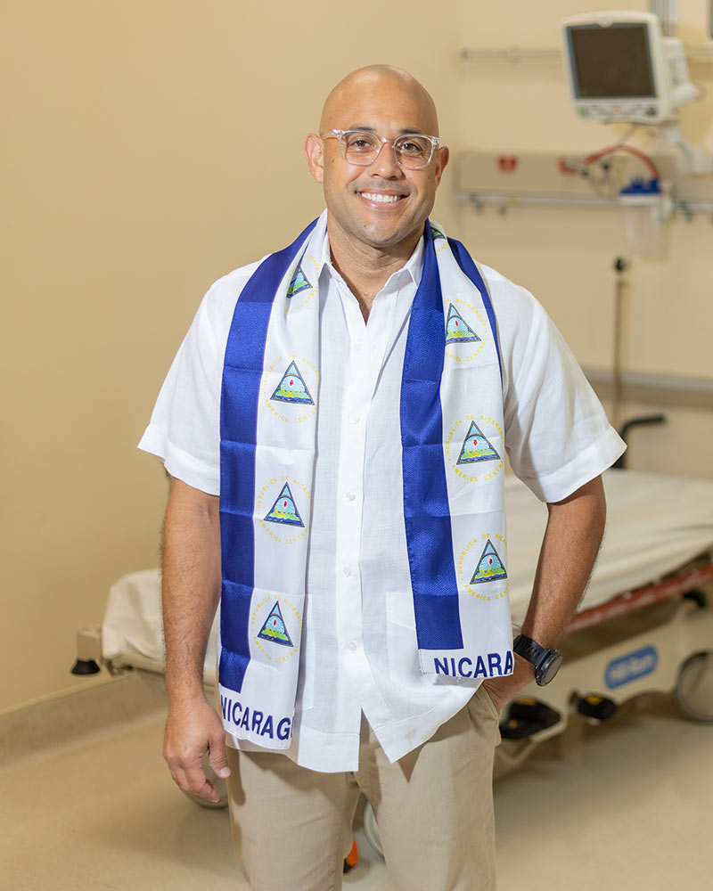 A man smiling at the camera, he wears a white shirt and a Nicaragua wrap