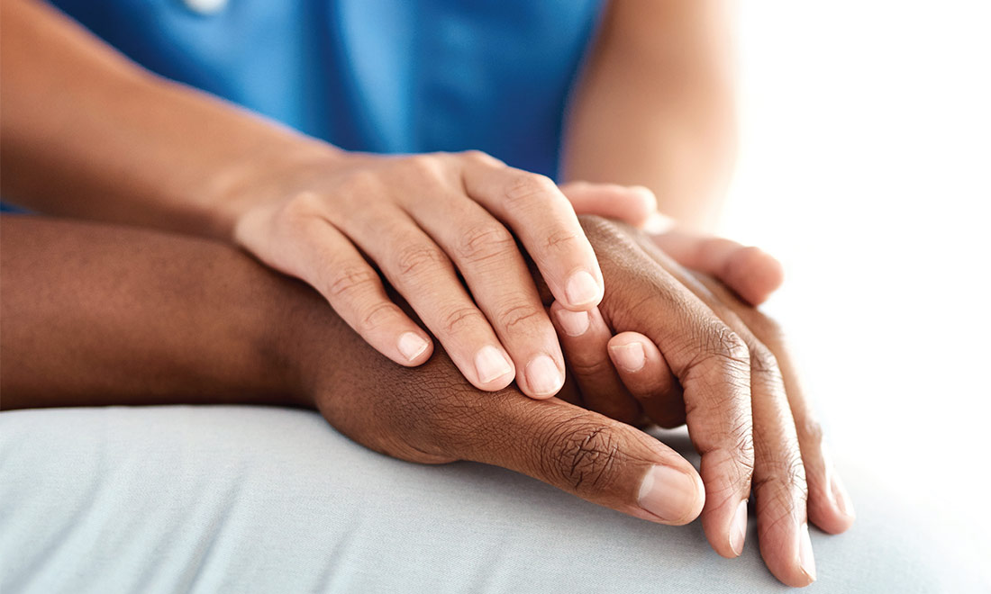 Closeup of a physicians hands holding a patients hand