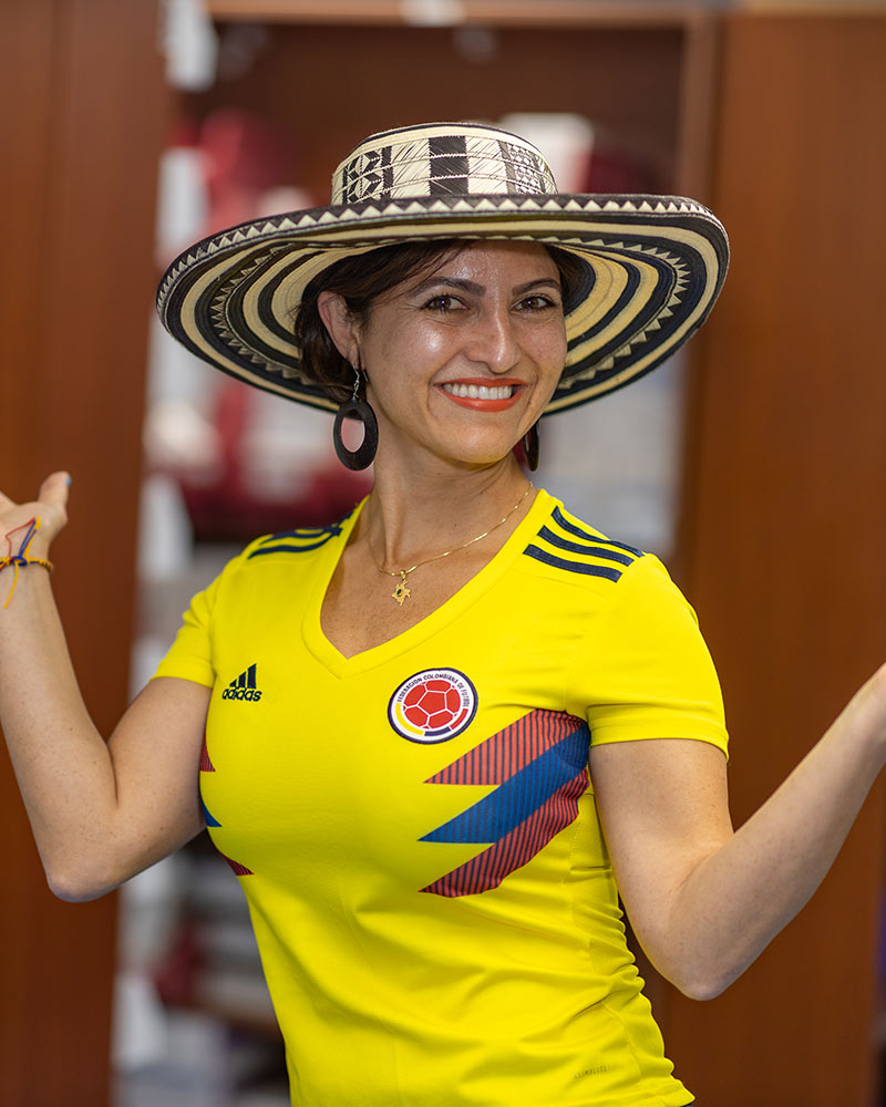 A woman wearing a yellow and red soccer jersey and wearing a hat