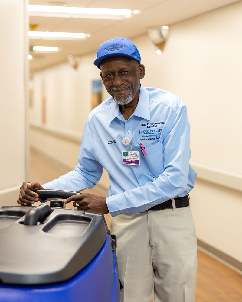 An older male smiling at the camera wearing a blue hat, a blue collar long sleeve shirt and kaki pants, he is pushing a large machine