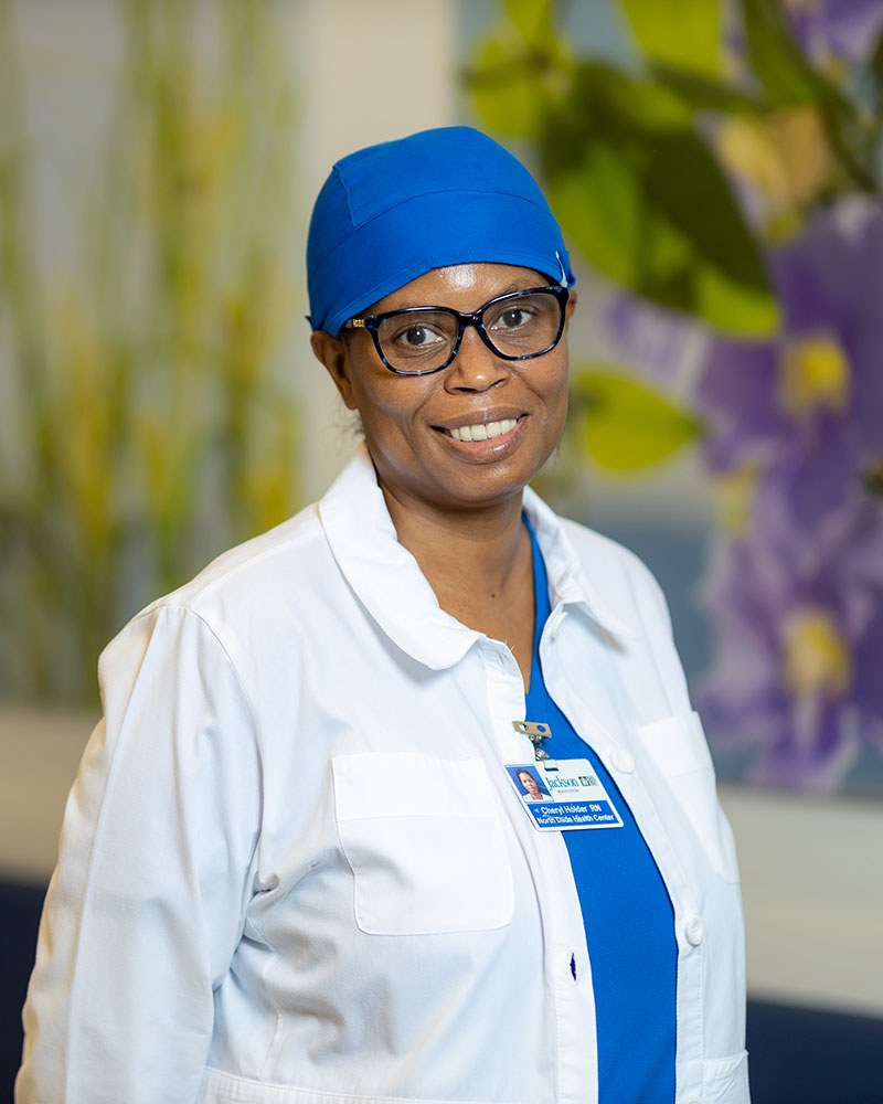 A woman smiling at the camera, she has on blue scrubs, a white medical jacket, and a blue cap