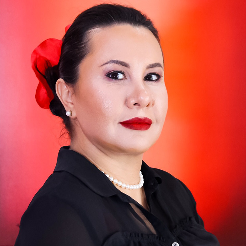 A closeup of a woman, she is wearing a black blouse, has on red lipstick, and has her hair pulled back