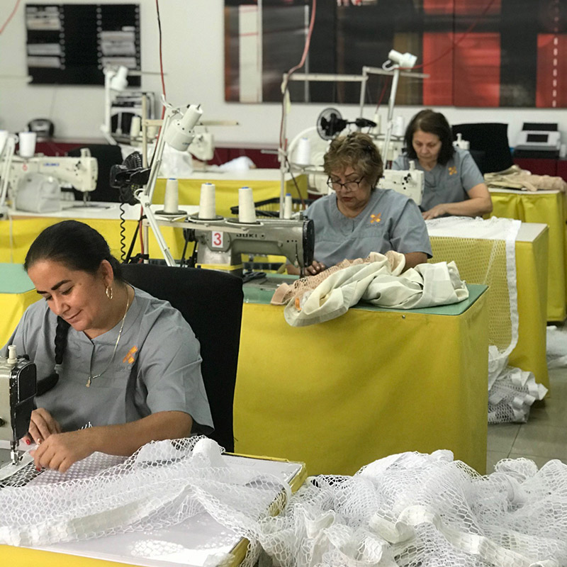 Three woman working on sewing machines inside a sewing machine room